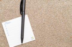 Wit stuk van document met geschreven plan op overzees zand, bedrijfsconcept Stock Fotografie