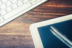 Wit Tablet en Grey Pencil Lying Next To een Wit Toetsenbord op Houten Lijst stock foto's