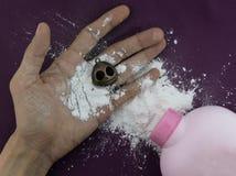 Wit talkpoeder met skeletstuk speelgoed op hand Stock Foto