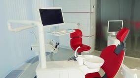 Wit tandartsbureau Binnenland van de luxe het minimalistic tandkliniek met rode stoel en hulpmiddelen, tandlamp over glasmuren stock footage