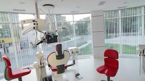 Wit tandartsbureau Binnenland van de luxe het minimalistic tandkliniek met rode stoel en hulpmiddelen, tandlamp over glasmuren stock video