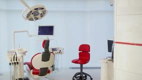 Wit tandartsbureau Binnenland van de luxe het minimalistic tandkliniek met rode stoel en hulpmiddelen, tandlamp over glasmuren stock videobeelden