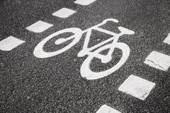 Wit teken dat van fiets en witte pijl één manier op asfaltweg richt Het witte weg merken stock foto
