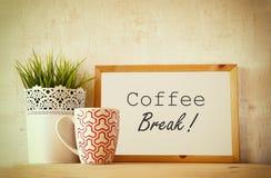 Wit tekenbord met de uitdrukkingskoffiepauze over houten lijst met coffekop en de decoratie van de bloempot Gefiltreerd beeld royalty-vrije stock fotografie