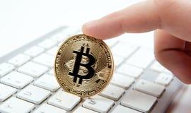 Wit toetsenbord en gouden muntstuk bitcoin in de hand van een mens Stock Foto's