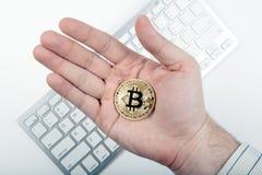 Wit toetsenbord en gouden muntstuk bitcoin in de hand van een mens Royalty-vrije Stock Afbeelding
