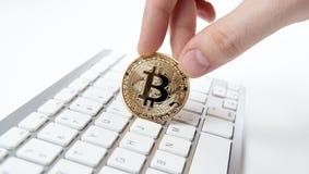 Wit toetsenbord en gouden muntstuk bitcoin in de hand van een mens Royalty-vrije Stock Foto's
