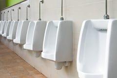 Wit urinoir in mensen` s badkamers Stock Afbeelding