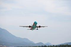 Wit vliegtuig die met wolken in de blauwe hemel van start gaan stock foto