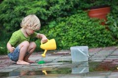 Wit weinig blootvoets meisje dat met water speelt Stock Afbeeldingen