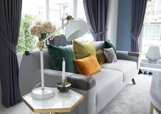 Wit woonkamerbinnenland met gele, blauwe en roze hoofdkussens op bank royalty-vrije stock foto's