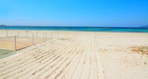 Wit zand en blauw water in Alghero-overzeese kust stock afbeeldingen