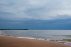 Wit zandstrand met golven en blauwe hemel op koude de zomerdag stock afbeeldingen