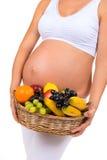 Witaminy jedzenie Ciężarny brzuch i kosz egzotyczne owoc Obrazy Stock