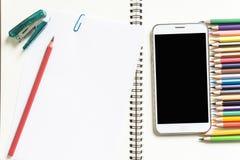 Witboek, kleurpotloden, en de telefoon op het bureau Royalty-vrije Stock Foto