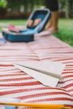 Witboekvliegtuig met Geopende Koffer en Heerser op de Witte en Rode Strepenmat Stock Fotografie