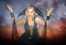 Witch. Blond lady in Halloween witch costume on the smoky hell background. Natural smoke was produced by smoking machine Royalty Free Stock Image