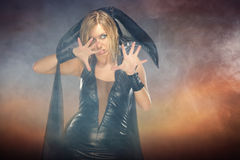 Witch. Angry woman in the witch costume on the colorful smoky background. Natural smoke produced by smoking machine Royalty Free Stock Photos