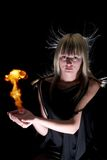 Witch. Young girl-witch with fire in hands, on black Royalty Free Stock Images