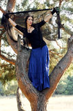 Witch. Girl-witch in the fork of a tree Royalty Free Stock Image