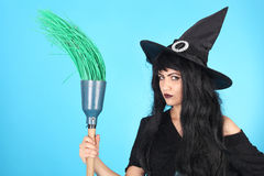 Witch. Pretty young witch on the blue background royalty free stock images