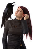 Witch. Young woman looking like a witch in black clothes with big raven on her shoulder, isolated on white Stock Photo