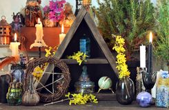 Witch altar with pentagram, spring flowers, black candles. Wicca, esoteric, divination and occult concept with vintage magic objects for mystic rituals royalty free stock photography