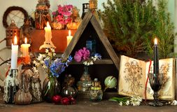 Witch altar table with magic book, flowers and spiritual objects. Wicca, esoteric, divination and occult concept with vintage magic objects for mystic rituals royalty free stock photography