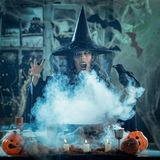 Witch Sends Evil Makes. Witch with awfully face and blackbird in her hand in creepy foggy surroundings full of cobweb sends evil. Halloween concept Royalty Free Stock Images