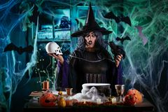 Witch Sends Evil Makes. Witch with awfully face in creepy surroundings full of cobweb with skull in one and blackbird in the other hand sends evil thoughts royalty free stock image