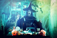 Witch Sends Evil Makes. Witch with awfully face and hat on her head in creepy surroundings full of cobweb sends evil. Halloween concept Stock Photo