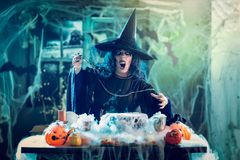 Witch Sends Evil Makes. Witch with awfully face and hat on her head in creepy surroundings full of cobweb sends evil. Halloween concept Royalty Free Stock Image