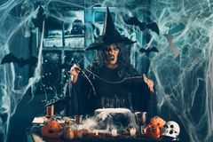 Witch Sends Evil Makes. Witch with awfully face and hat on her head in creepy surroundings full of cobweb sends evil. Halloween concept Royalty Free Stock Photo