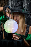 witch on a black background with a magic ball Stock Photos