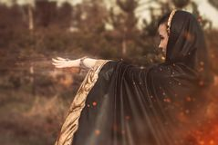 The witch in a black cloak uses magic. An enchantress in the woods, the witch in a black cloak uses magic royalty free stock photo