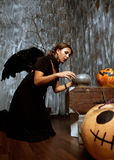 Witch with black wings practice witchcraft over the pot to brew Stock Photography