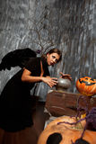 Witch with black wings practice witchcraft over the pot to brew Royalty Free Stock Photos