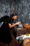 Witch with black wings practice witchcraft over the pot to brew Royalty Free Stock Photography