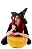 Witch with bloodstained hands with a hatchet in hand sits on a p Royalty Free Stock Images