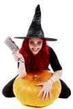 Witch with bloodstained hands with a hatchet in hand sits on a p Stock Images