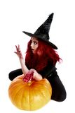 Witch with bloodstained hands with a hatchet in hand sits on a p Royalty Free Stock Photo