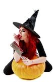 Witch with bloodstained hands with a hatchet in hand sits on a p Stock Photo