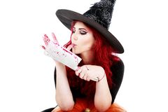Witch with bloodstained hands with a hatchet in hand sits on a p Stock Photography