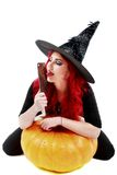 Witch with bloodstained hands with a hatchet in hand sits on a p Stock Image
