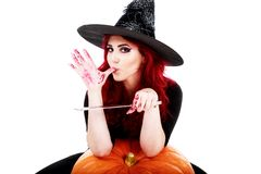 Witch with bloodstained hands with a hatchet in hand sits on a p Stock Photos