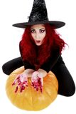 Witch with bloodstained hands with a hatchet in hand sits on a p Royalty Free Stock Photos