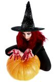 Witch with bloodstained hands  sits on a pumpkin Royalty Free Stock Images