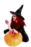 Witch with bloodstained hands  sits on a pumpkin Royalty Free Stock Photo