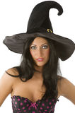 Witch with blue eyes. Beautiful and sensual brunette with blue eyes and hat of witch on Royalty Free Stock Photo