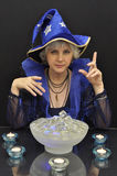 Witch in blue hat with magic crystals and candles Stock Image